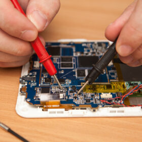 repairer is looking for damage to the tablet using a multimeter.