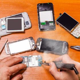 soldering, repair broken phone on a wooden background