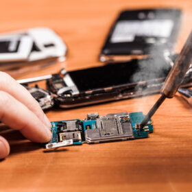 soldering, repairing fractured phone on a wooden background